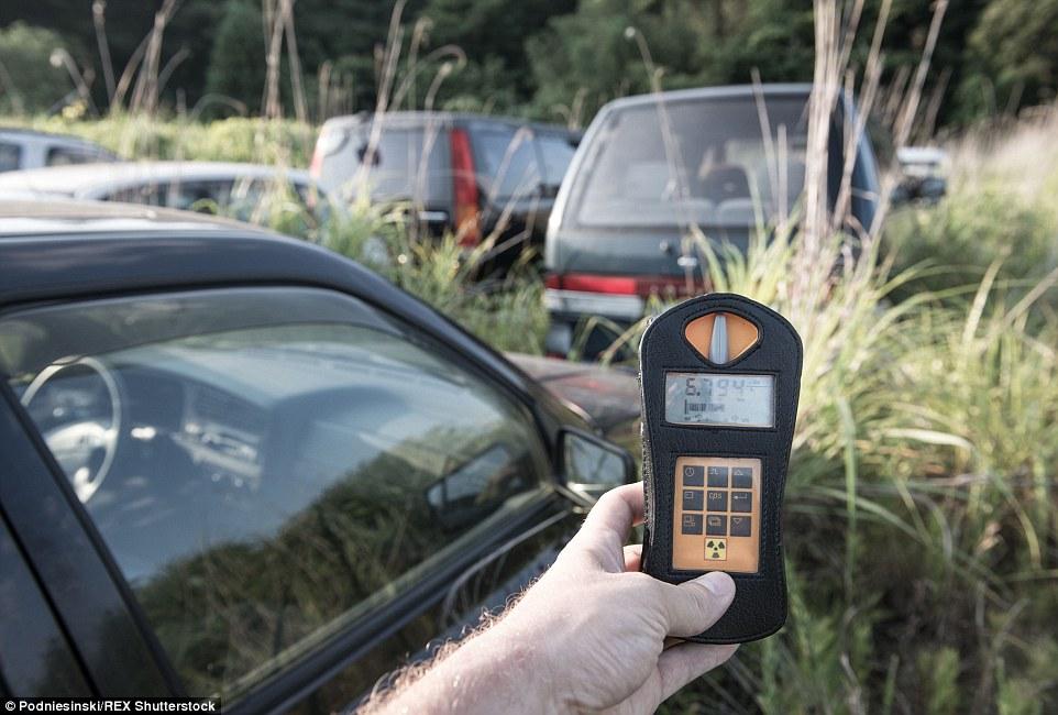 Photographer Arkandiusz Podniesinski shows a radiation reading of 6.7 uSv/h inside the dangerous fallout zone