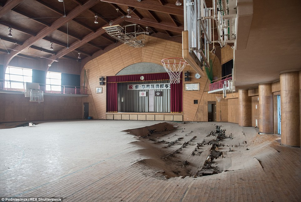 The disaster was triggered by an earthquake which generated the tsunami. Pictured is a school gymnasium damaged by the shaking