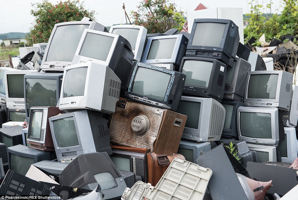 A stack of contaminated televisions lie in a heap among the overgrown forests and abandoned buildings near Fukushima