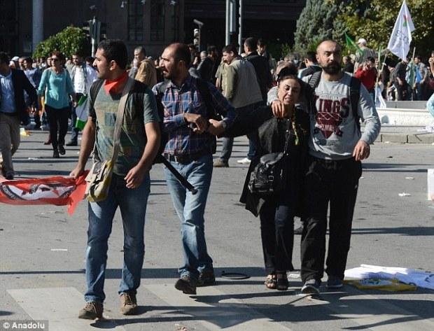 Struggling: Shocked demonstrators comfort each other after the devastating blast which left 400 injured