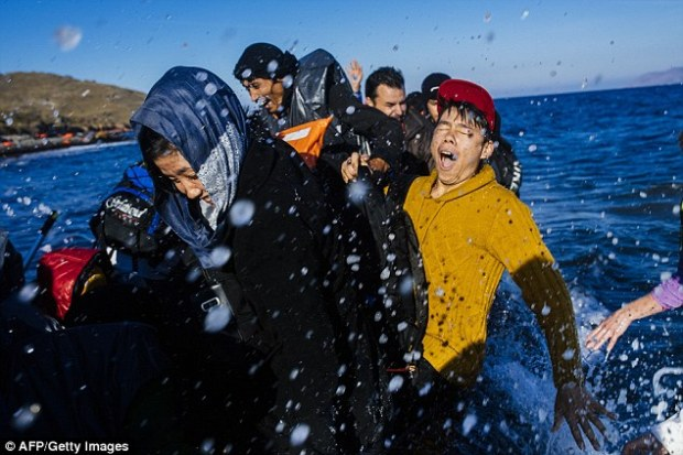 Refugees reach the Greek island of Lesbos on a rubber dinghy yesterday - EU member states hope talks with Turkey will help ease the migrant crisis