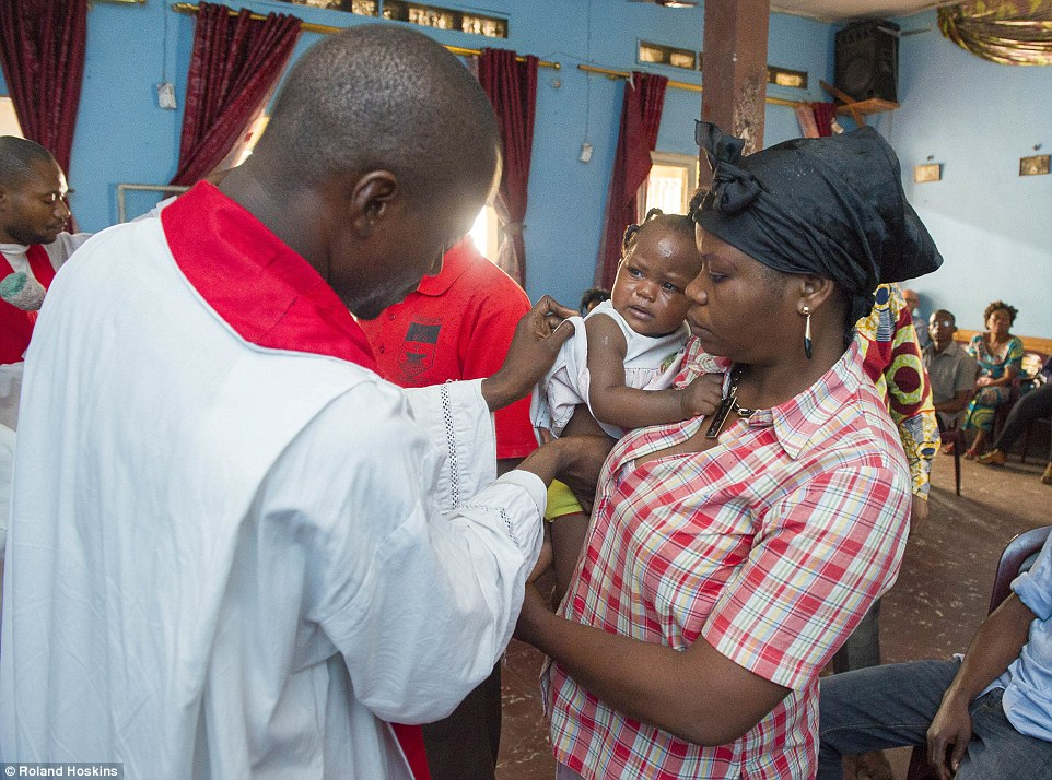 Confused: Eleven-month-old baby Grace endures an exorcism at a Catholic church in Kinshasa, DRC
