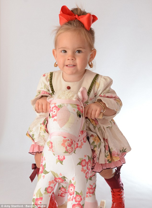 Minnie owns 300 designer dresses and has a full wardrobe, pictured riding a floral rocking horse