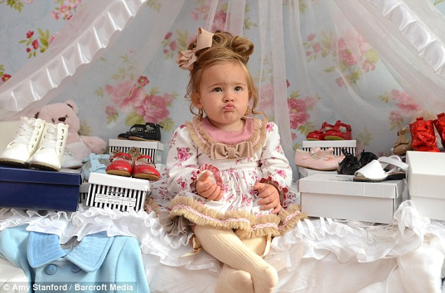 The toddler surrounded by her £600 collection of shoes in her girly bedroom decorated with florals