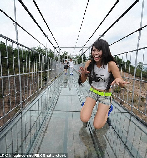 A 590ft high glass-bottomed suspension bridge in Hunan, central China