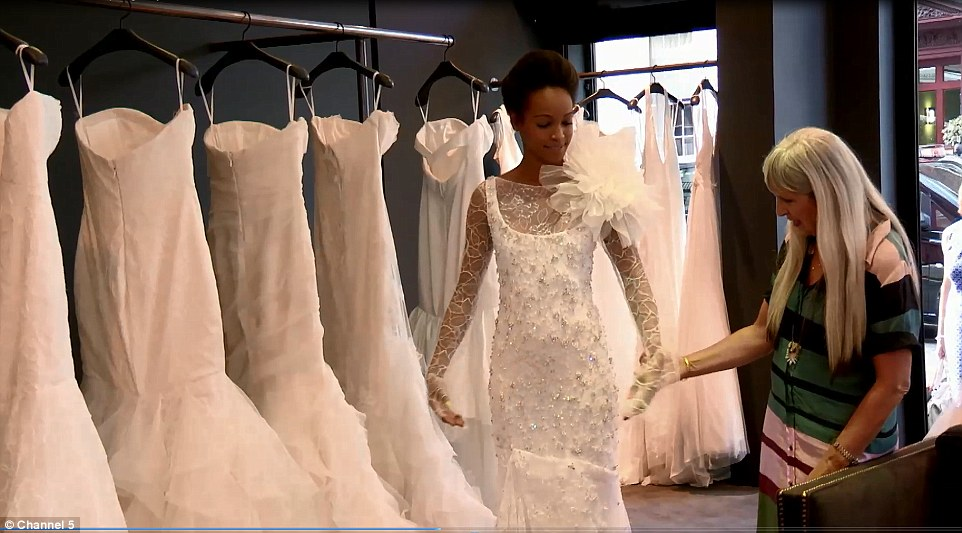 A model tries on a Vera Wang wedding gown worth £100,000, such dresses are in demand with Nigerian brides