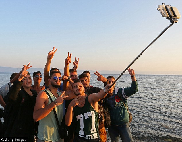 A group of young men Refugees flash victory sign as they pose for a selfie on the shore of Eftalou beach, Lesbos, after crossing the Aegean from Turkey last month