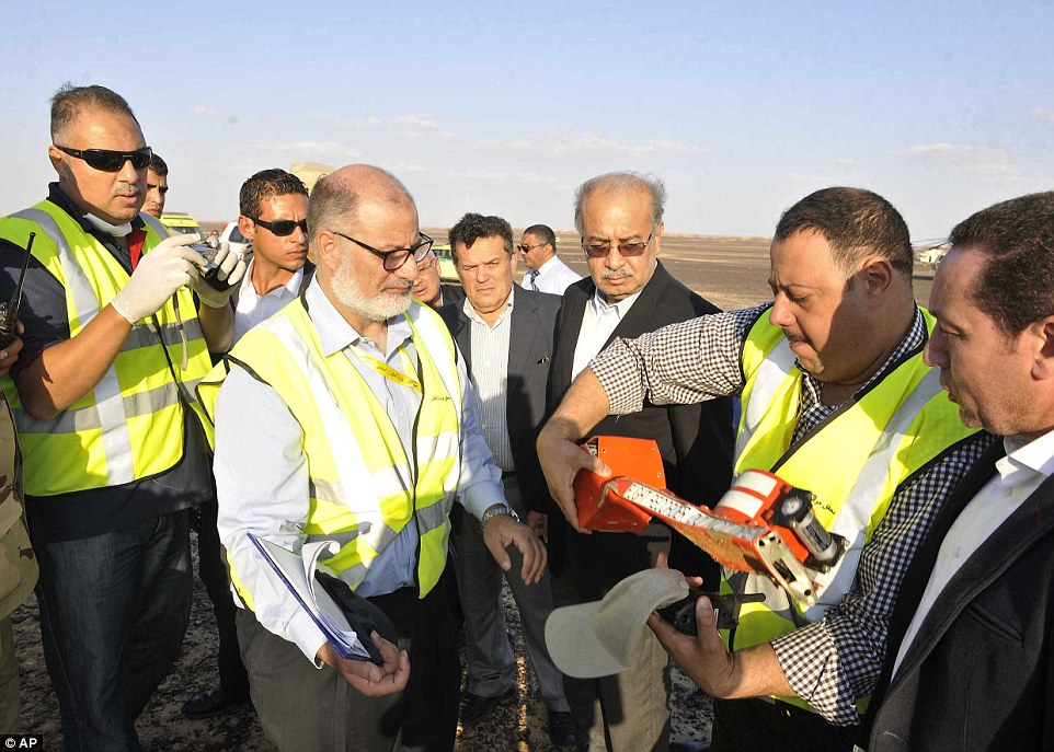 Recorder: In this image released by the Prime Minister's office, Mr Ismail, third right, observes the plane's flight data recorder with officials