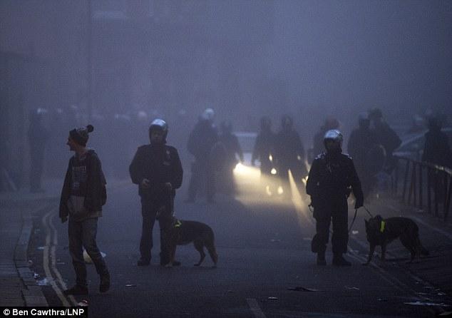 Bajo ataque: la policía antidisturbios (en la foto con los perros) fueron una lluvia de misiles y una bomba de gasolina sospecha