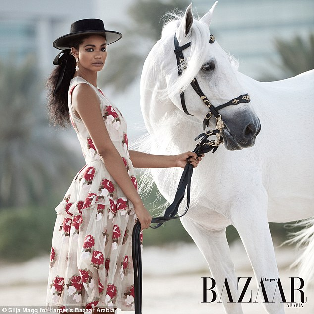 Going the distance: Switching into a series of different looks, the beautiful catwalk star also wears a pretty white dress which is embellished with sequin flowers throughout, teaming it with black headwear