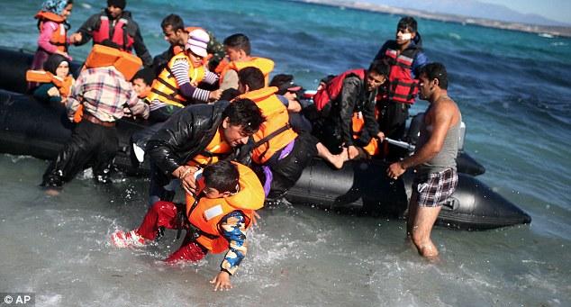 Un hombre levanta a un niño desde el barco de goma en las aguas poco profundas agitadas después que el grupo decidió no hacer el viaje