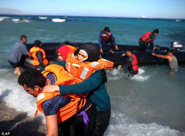 Una mujer garras en que la camiseta de otro migrante y chaleco salvavidas, ya que desembarcan del bote