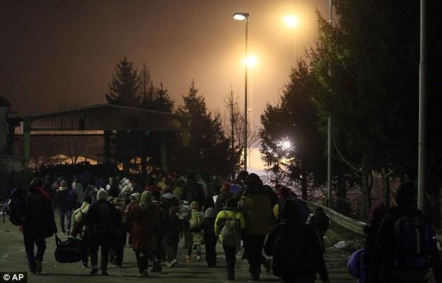 Mientras cientos esperaban, otros cruzaron la frontera entre Eslovenia y Austria llevar grandes bolsas y vestidos con ropa de invierno