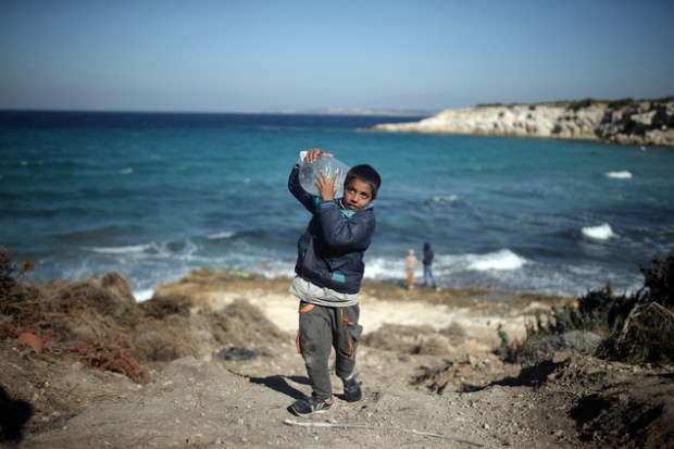 A boy carries a can of water near a beach from where migrants are traveling by dinghies to the Greek island of Chios from Turkish coast near Cesme, Izmir, Turkey