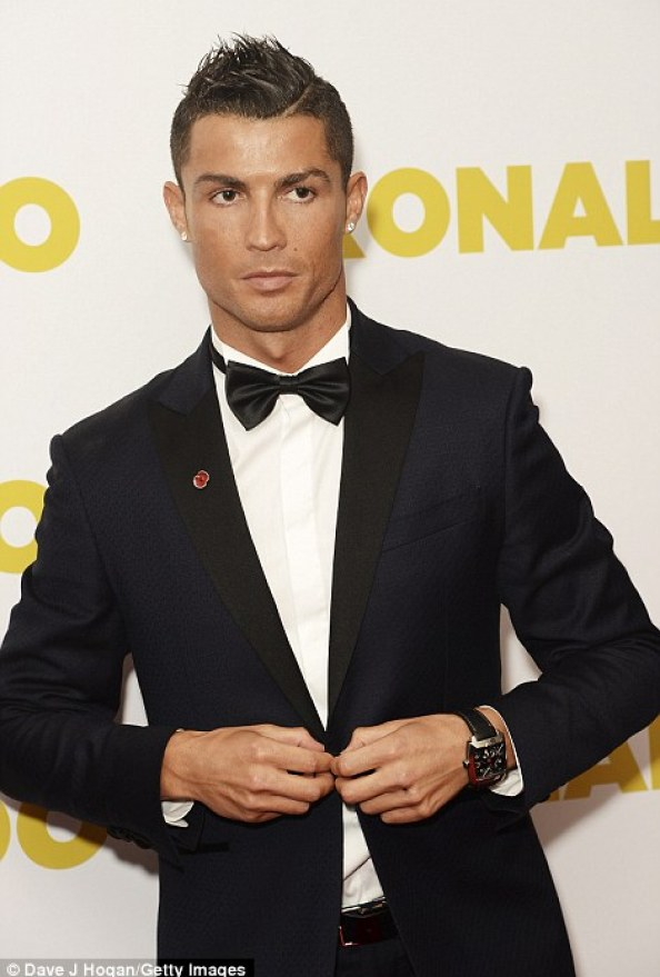 Ronaldo adjusts his suit jacket inside