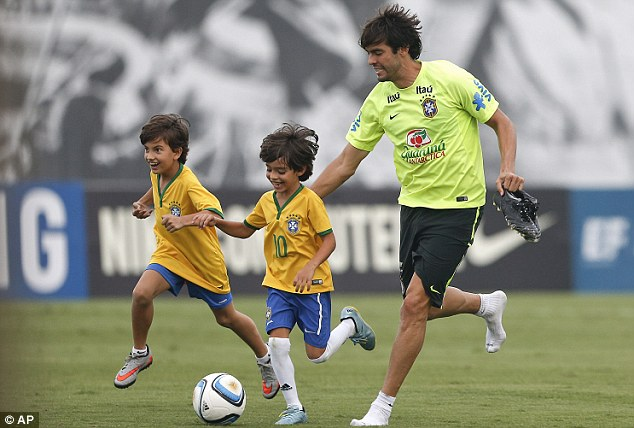 Brazil's Kaka plays with his son Luca (centre) during a training session in Sao Paulo on Tuesday
