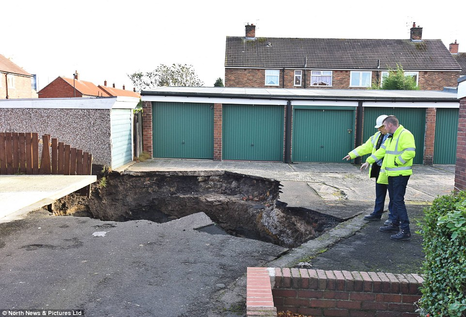 No one was injured when the 20ft crater (pictured) suddenly appeared, although police and officials remain at the site this afternoon