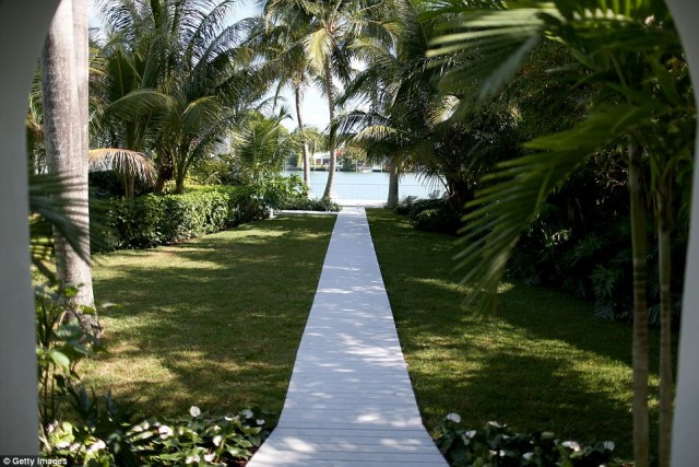 A walkway leading to the pool and a small beach area in front of the home