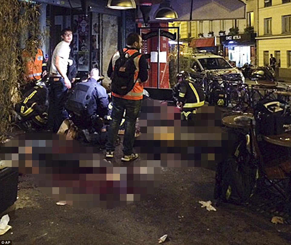 Victims of the shooting attack lay on the pavement with medics outside La Belle Equipe restaurant in Paris