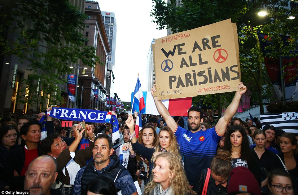 In Sydney, Australia, hundreds took to the streets waving French flags and holding banners proudly proclaiming 'We are all Parisians' as people across the world took part in vigils honouring those killed in last night's terror attacks in Paris