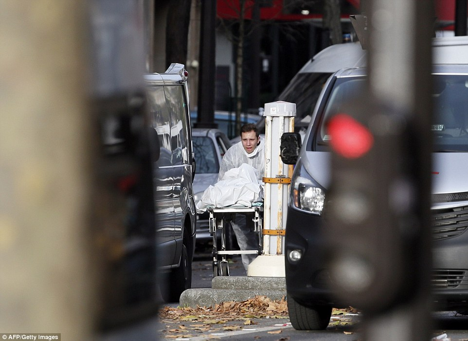 A medic takes a victim's body away from the scene of the Bataclan concert hall where up to 100 fans were shot dead at a heavy metal gig