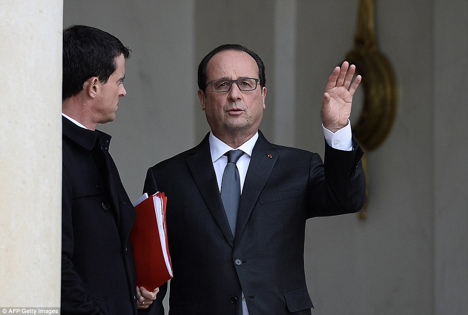 President Francois Hollande speaks to French Prime minister Manuel Valls while leaving the Elysee Palace in Paris after a security meeting