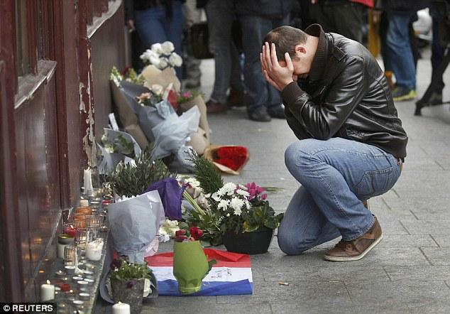 Un duelo paga sus respetos fuera del restaurante Le Carillon, el sitio de uno de los ataques