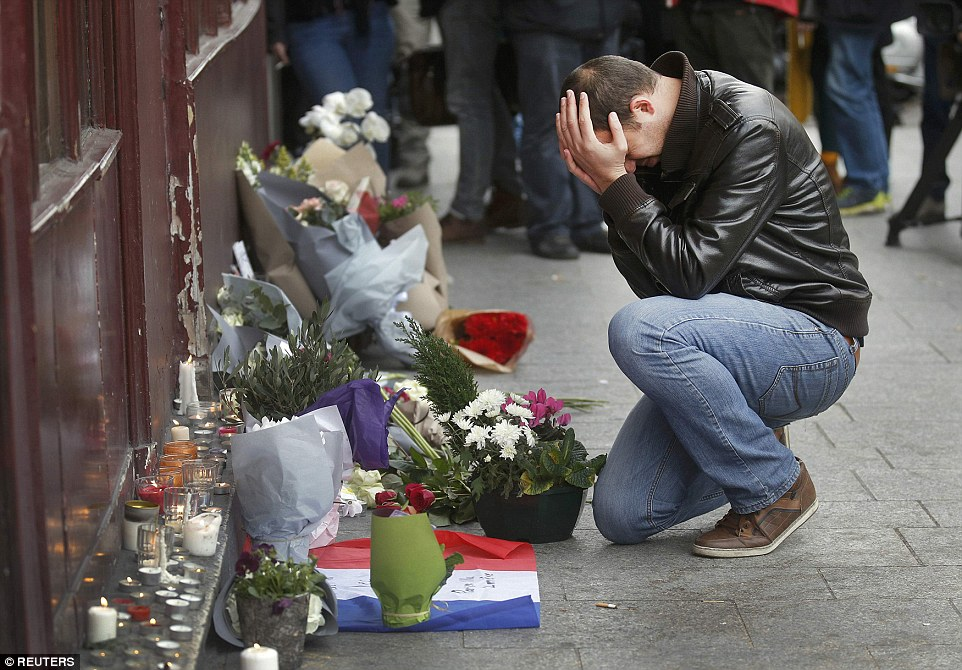 A mourner pays his respect outside the Le Carillon restaurant the morning after a series of deadly attacks in Paris that killed at least 127