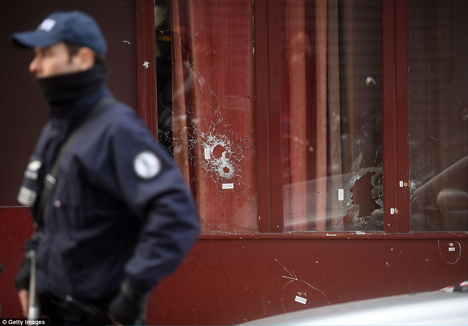 Bullet holes are seen in the windows of Le Carillon bar after gunmen targeted a string of businesses, killing more than 20 people