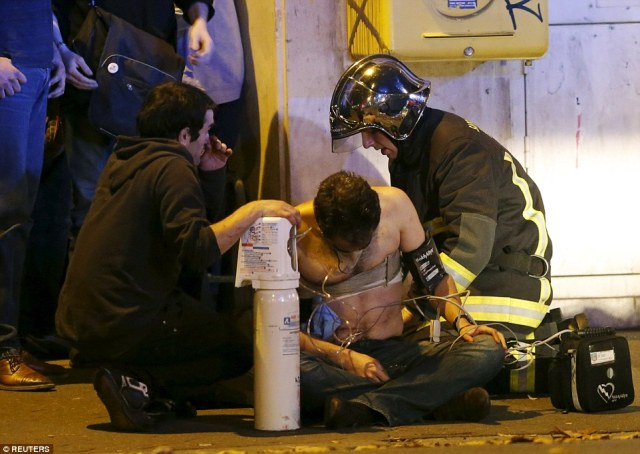 A fireman administers first aid to one of the concert-goers caught up in the shooting inside the Bataclan concert hall