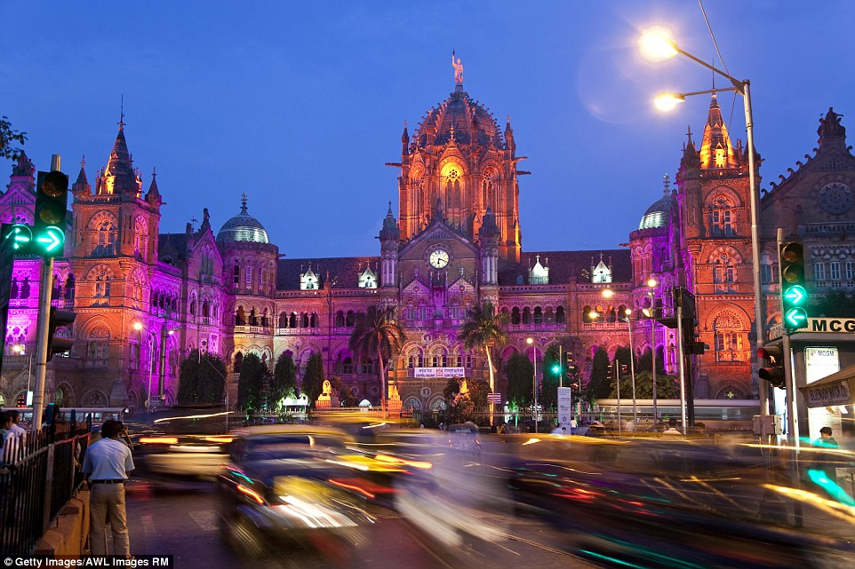 Victoria Terminus in Mumbai is lit up in glorious shades of purples and reds (above) but it's beautiful architecture is left plain in the day