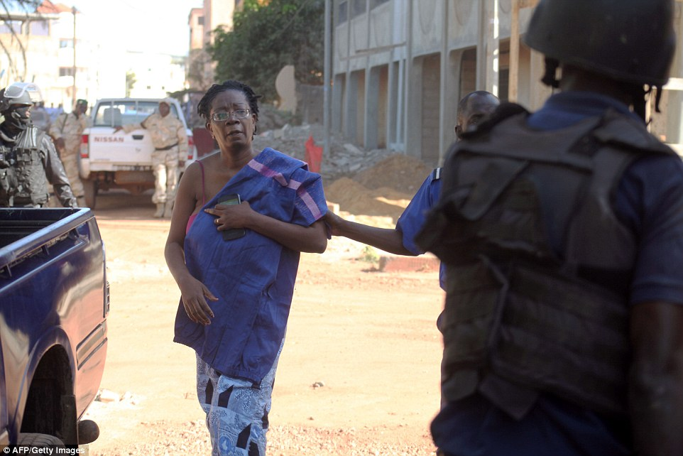 Police officers tend to a woman at the scene following the shocking events inside the hotel
