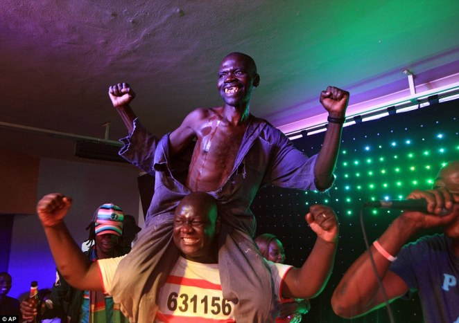 Mr Sere is pictured on a friend's shoulders with his overalls hanging down as he celebrates his win and after scooping $500