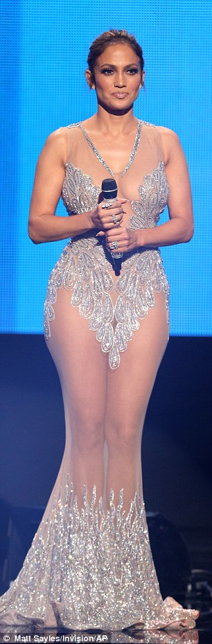 Revealing: The singer flashed her bra in a sheer black gown, then showed off her hourglass figure in a silver, see-through gown with long train