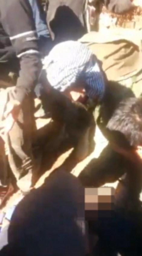 Al menos una docena de hombres rodean el cadáver del piloto, vestido con uniforme militar de Rusia, y algunos se oyen gritar 'Allahu Akbar'