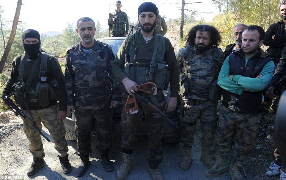 Una imagen ha surgido de Alpaslan Celik (centro), un subcomandante de una brigada de Turkmenistán sirio, sosteniendo las manijas que se consideran partes de un paracaídas que pertenecen a un piloto del avión de combate ruso derribado