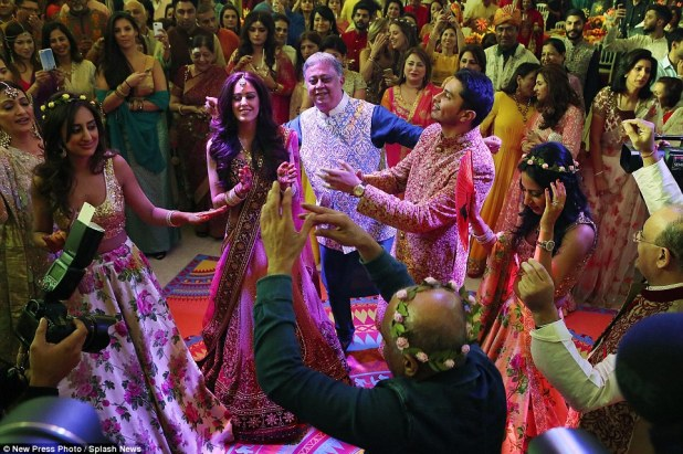 Guests wore traditional Indian dress, with the bride and groom taking centre stage in front of groom's father Yogesh Mehta (centre in blue)