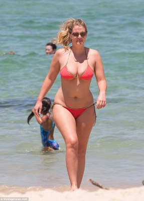Life in the sun: Lady Kitty Spencer is spotted enjoying a day out on Bondi Beach. Kitty, niece of the late Princess Diana, was sporting a tiny peach bikini as she and a mystery man took a dip in the ocean before heading off for lunch