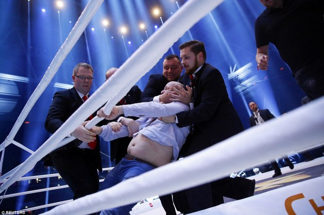 Four security staff in suits had to restrain a supporter who had invaded the ring after the fight had been decided