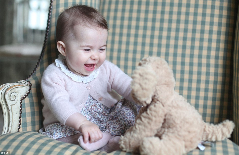 Snapped by her adoring mother, the Duchess of Cambridge, this is little Princess Charlotte at six months old. The princess can be seen sitting unaided in a green checked armchair and in one shot is smiling at a toy puppy