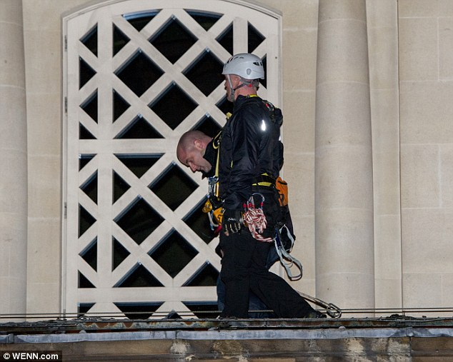 One of the fathers' rights campaigners is led away by an officer, who is clad in climbing gear and a hard hat