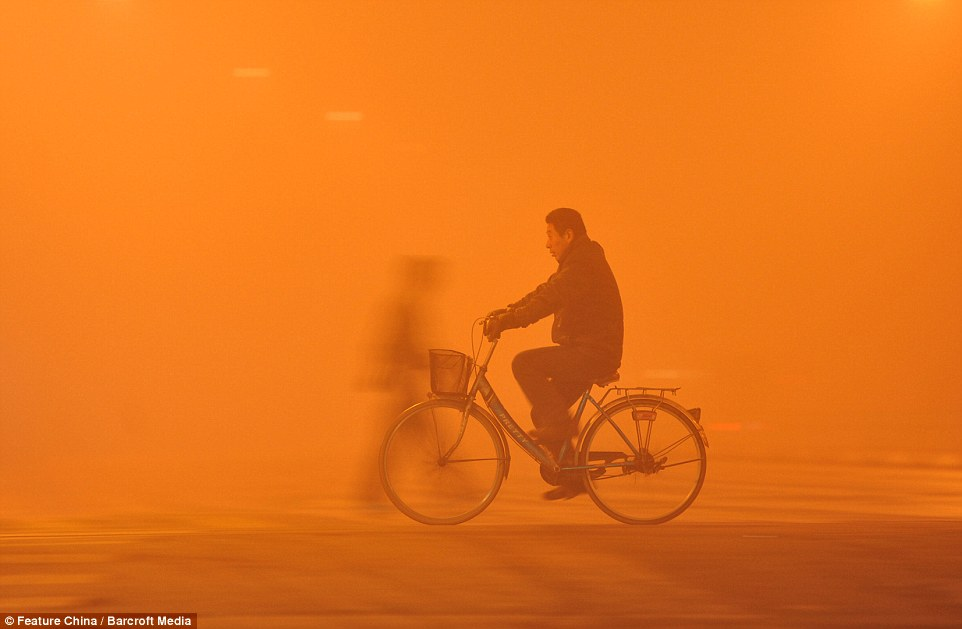 A man rides through the smog in Fuyang, China. Emissions in northern China soar over winter as urban heating systems are switched on