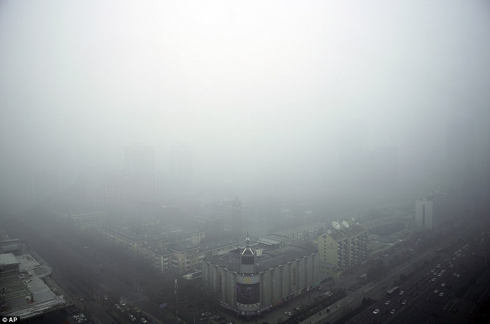 Visibility: Buildings in Beijing are barely visible through the smog in the city this morning.  The second-highest air alert has been triggered