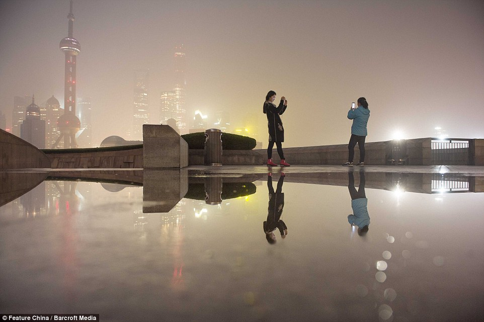 Tourists take photos on the Bund in Shanghai, China.Greenpeace found nearly 80 per cent of cities in the country have had pollution levels that 'greatly exceeded' national standards over the first nine months of this year