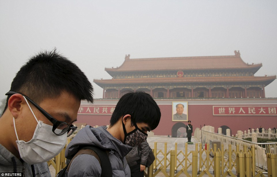 People wearing masks walk past the giant portrait of late Chinese Chairman Mao Zedong at Tiananmen Gate in Beijing today