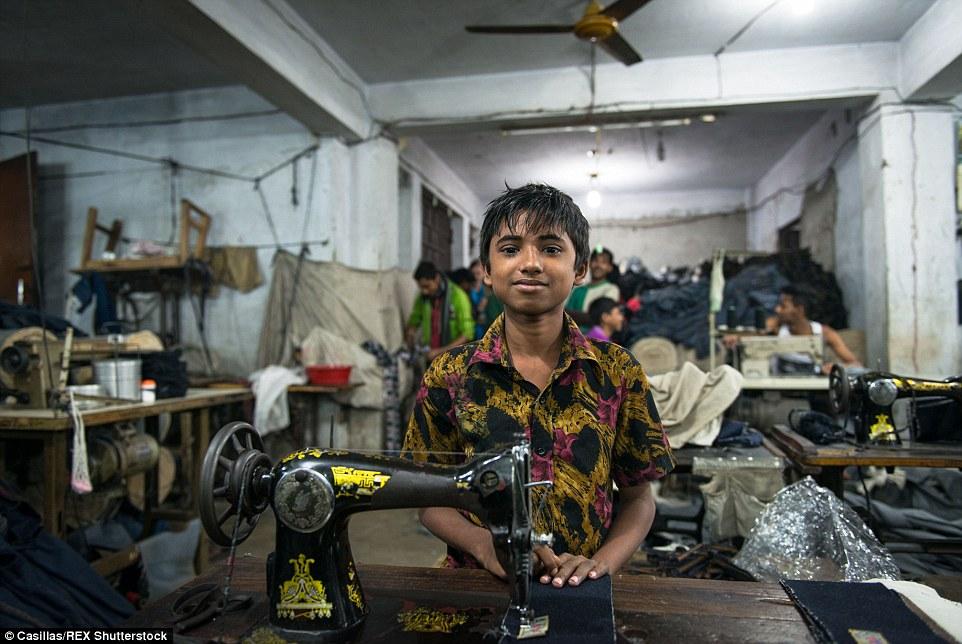Una joven trabajadora de la confección en su puesto de trabajo.  Su trabajo consiste en etiquetas de costura a los pantalones vaqueros azules.