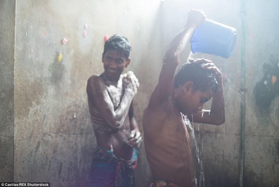 Trabajadores de la confección jóvenes que tienen una ducha dentro de su fábrica.  Debido a la carga de trabajo que comen, ducha y dormir dentro de estas fábricas.