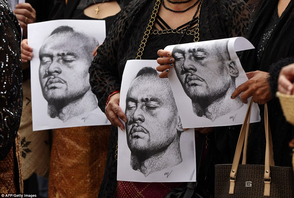 Portraits of Lomu's face, seemingly sketched in a peaceful pose with his eyes closed, are held by mourners