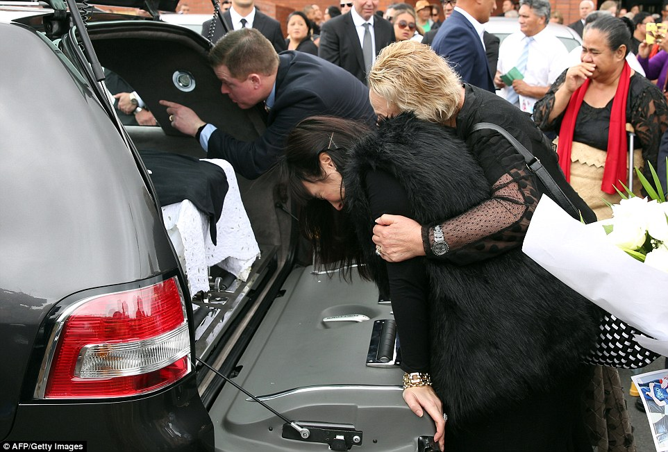 A heartbroken Nadene stands at the back of the hearse with her mother following the service at the church she attends