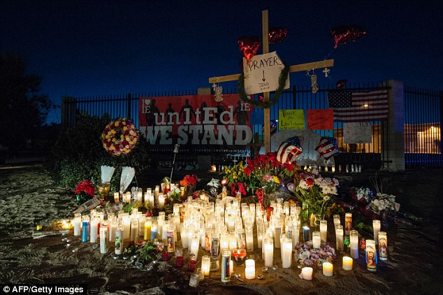 Candles burn before dawn at a growing makeshift memorial at Waterman Avenue and Orange Show Road near the Inland Regional Center, in San Bernardino, California, to honor the victims of the shooting